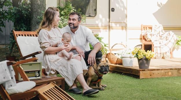 Gezin met baby en hond in de buurt van camper, op reis