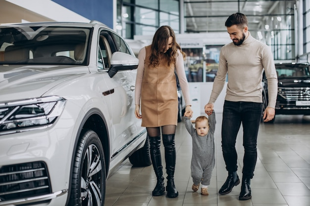 Gezin met babymeisje dat een auto kiest in een autosalon