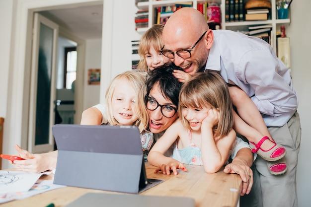 Gezin met drie kinderen binnen met behulp van tablet - samenhorigheid, technologie, entertainment concept