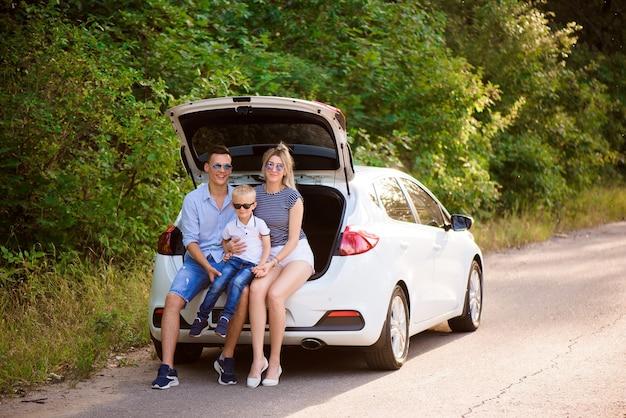 Gezin met een kind zittend in de kofferbak van een auto, zich voorbereiden op een zomerse reis naar de zee.