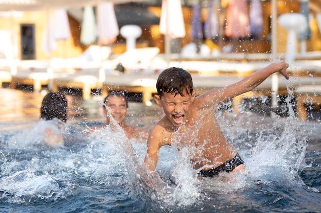 Gezin met jongen genieten van hun dag bij het zwembad swimming