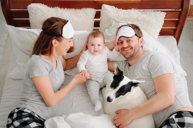 Gezin met kind en hond die samen in bed liggen jonge moeder en vader rustend met peuterkind...