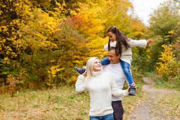Gezin met kind gaat in herfst park