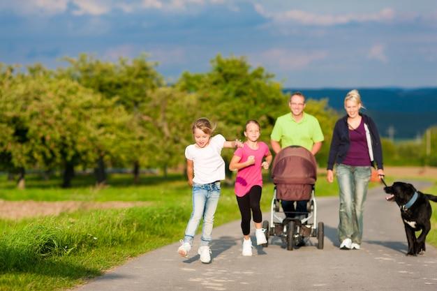 Gezin met kinderen en hond lopen
