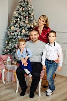Gezin met kinderen en kerstboom thuis