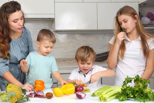 Gezin met kinderen gesneden groenten om te koken