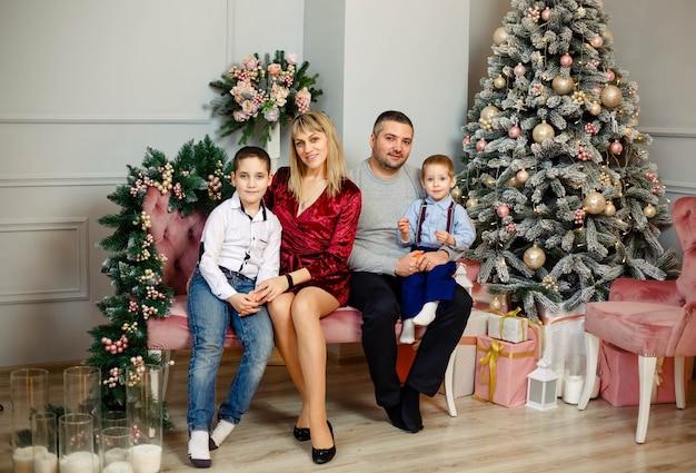 Gezin met kinderen in de buurt van de kerstboom