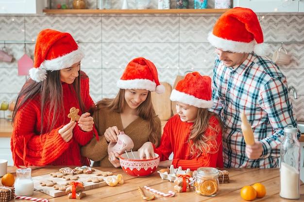 Gezin met kinderen koekjes voorbereiden op kerstmis in de keuken. prettige kerstdagen en fijne feestdagen.