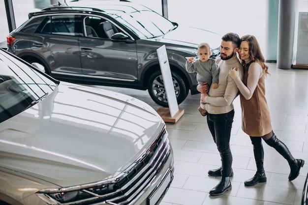 Gezin met peutermeisje dat een auto kiest in een autoshowroom