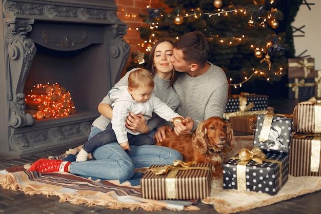 Gezin met schattige hond thuis in de buurt van kerstboom