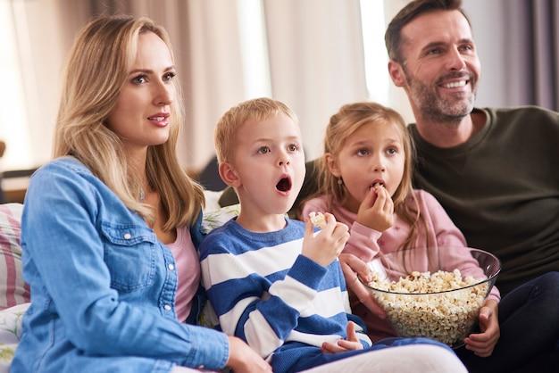 Gezin met twee kinderen die tv kijken in de woonkamer