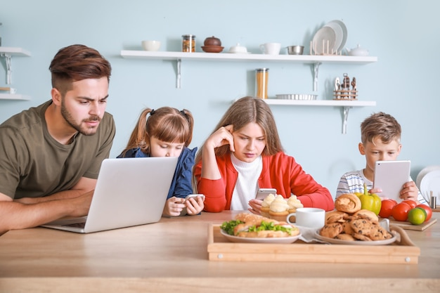 Gezin met verslaving aan moderne technologieën, zittend aan tafel in de keuken