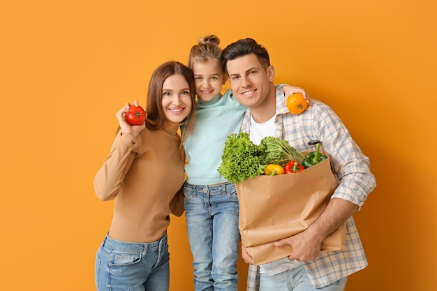 Gezin met voedsel in zak op kleur