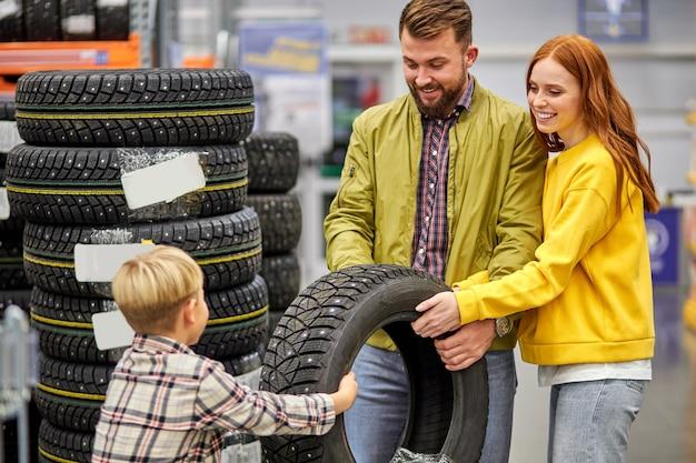 Gezin met zoon die autoband in winkel kiezen, samen een keuze maken, plezier maken, winkelconcept