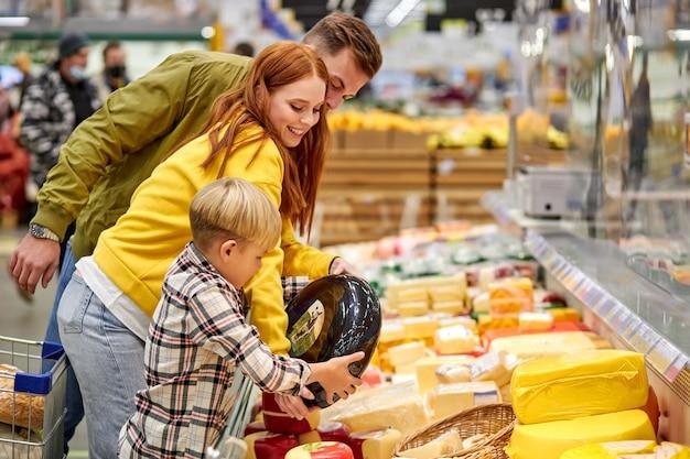 Gezin met zoon die verse groenten koopt, kies de beste, vrouw bespreekt de aankoop met echtgenoot