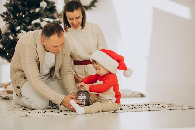 Gezin met zoontje bij de kerstboom thuis