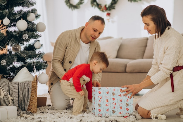 Gezin met zoontje op kerstmis door kerstboom thuis