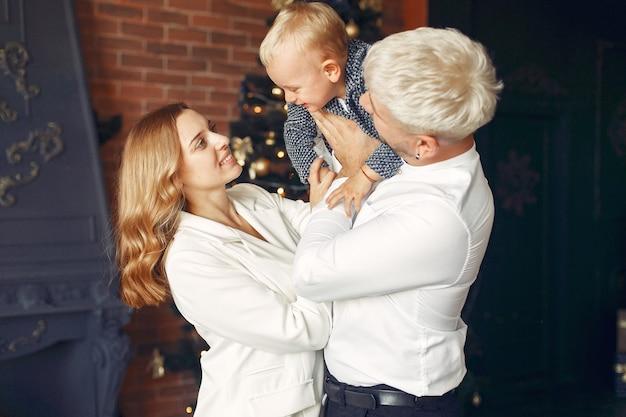Gezin met zoontje thuis in de buurt van kerstboom