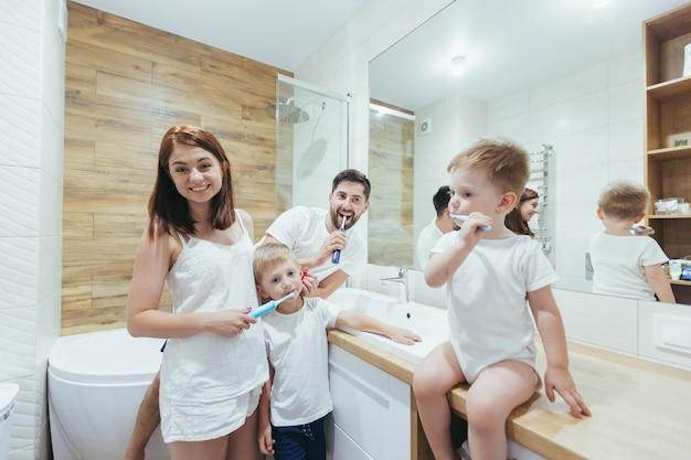 Gezin, twee volwassenen en twee kleine jongenskinderen poetsen samen hun tanden in de badkamer