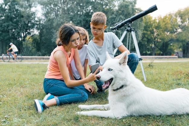 Gezin van drie kinderen wandelen in het park met husky witte hond