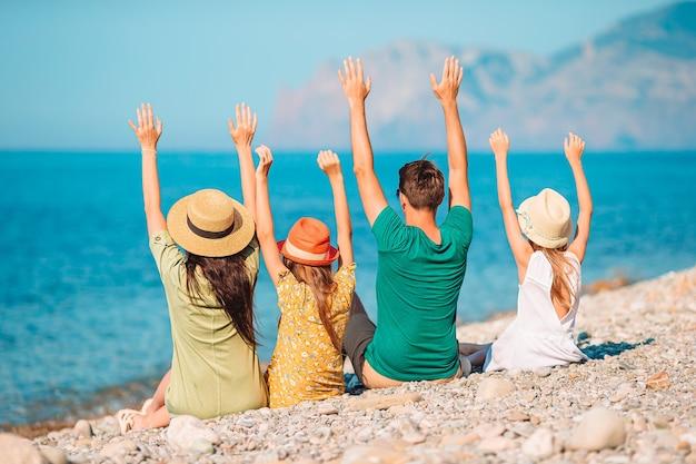 Gezin van vier personen die samen plezier hebben op het strand