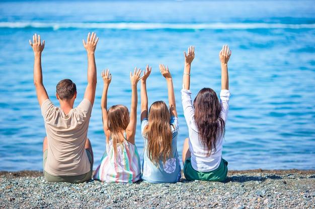 Gezin van vier personen heeft samen plezier op de strandvakantie