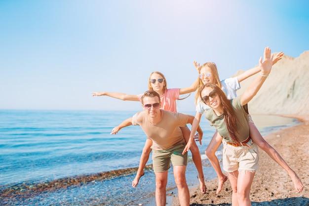 Gezin van vier plezier samen op het strand