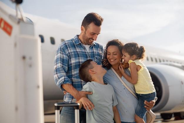 Gezin van vier ziet er opgewonden uit terwijl ze op reis gaan terwijl ze buiten voor een groot vliegtuig staan