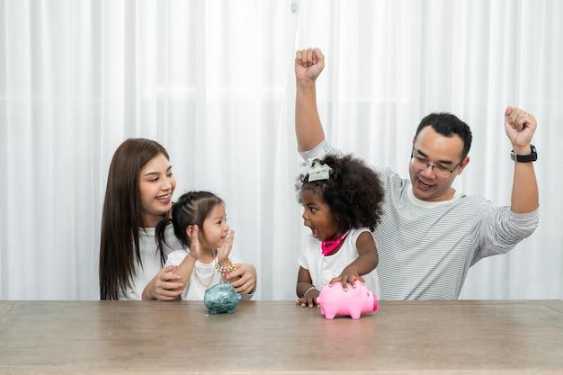 Gezinsbesparingen, budgetplanning, zakgeld voor kinderen, aziatische familie en geadopteerde afrikaanse dochter tonen spaarpot spaarpot