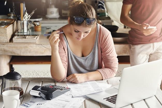 Gezinsbudget en financiële problemen. geconcentreerde bezorgde vrouw die thuis papierwerk doet, huishoudelijke uitgaven berekent en gas- en elektriciteitsrekeningen betaalt, met behulp van laptopcomputer en rekenmachine