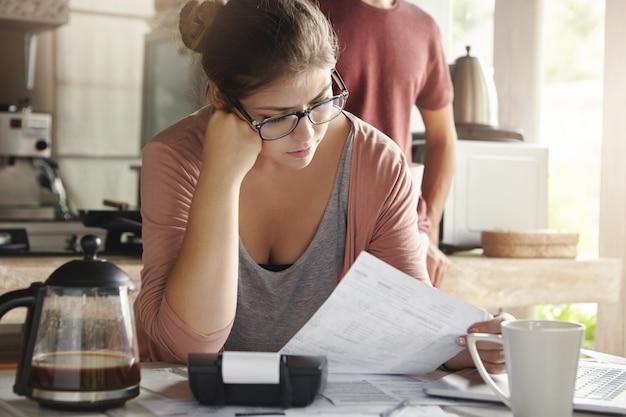 Gezinsbudget en financiën. ernstige vrouw die rekeningen doet en zich gefrustreerd voelt met het bedrag van de maandelijkse uitgaven. jong wijfje die glazen dragen die nutsrekeningen berekenen, die bij keukenlijst zitten