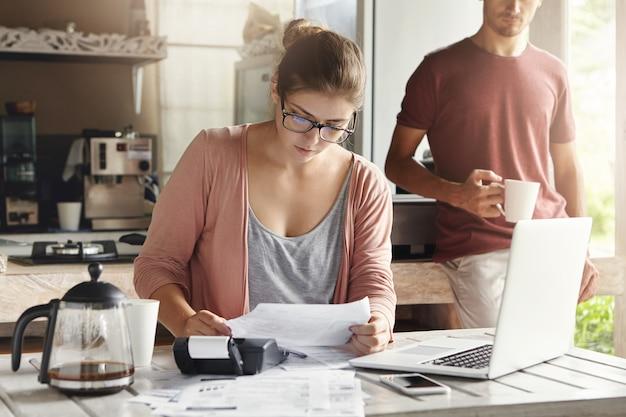 Gezinsbudget en financiën. jonge vrouw die rekeningen samen met haar echtgenoot thuis doen, die nieuwe aankoop plannen. ernstig wijfje in glazen die stuk van document houden en noodzakelijke berekeningen maken