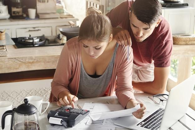 Gezinsbudget en financiënconcept. jonge ernstige vrouw en echtgenoot die rekeningen thuis samen doen