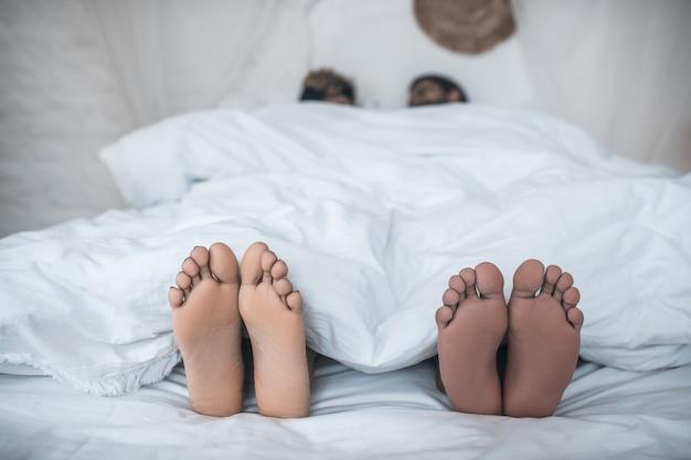 Gezinsgeluk. voeten van donkere huid man en vrouw uitkijken onder de witte deken op bed thuis in de ochtend