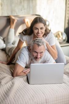 Gezinsleven. gelukkig grijsharige man en langharige vrouw in huiskleren met laptop thuis op bed in goed humeur