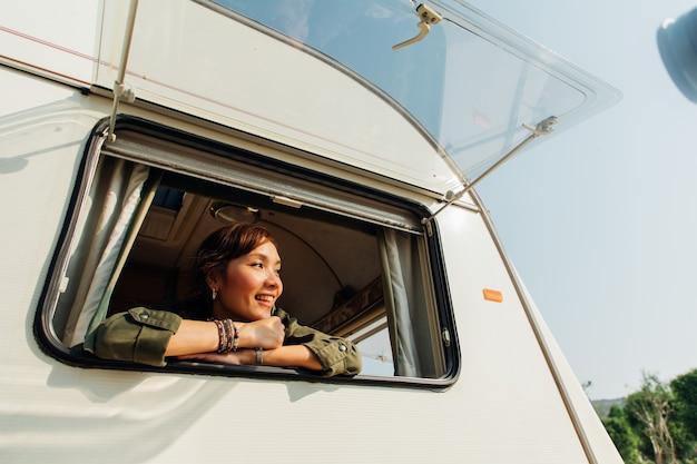 Gezinsreis met caravan op prachtige vakantie. jonge aziatische vrouw in caravan met witte koffiekop in de ochtend