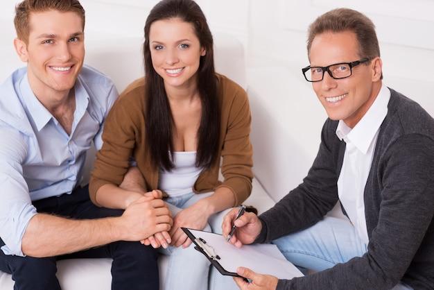 Gezinstherapie. bovenaanzicht van gelukkig jong stel en zelfverzekerde psychiater die bij elkaar zitten en glimlachen