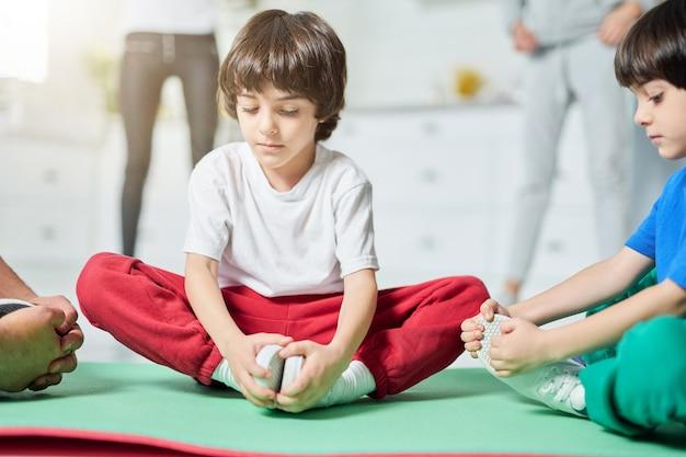 Gezinstraining twee schattige kleine spaanse jongens die in yoga zitten poseren op een mat terwijl