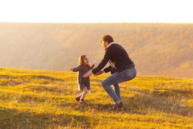 Gezinsvakantie. foto van vader die zijn dochter, weide of park op zonsondergang vangt