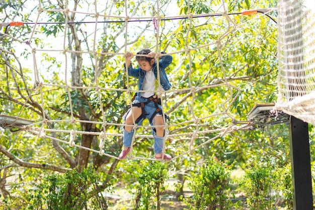 Gezond aziatisch tienermeisje dat van activiteit geniet in een klimavonturenpark in zomerkamp.