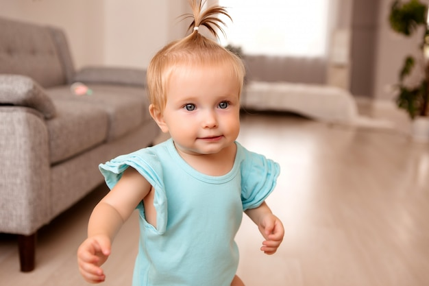 Gezond babymeisje in een kamer naast een grijze bank leert lopen