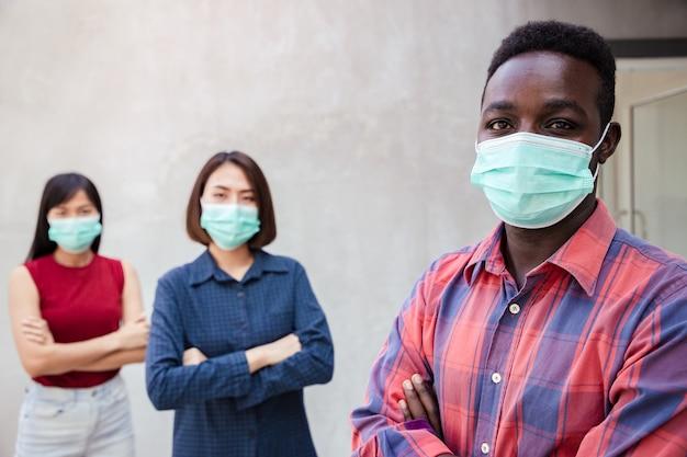 Gezond bedrijfsgroepswerk in groen medisch beschermend masker dat gebareinde toont. gezondheidsbescherming en preventie tijdens griep en besmettelijke uitbraak of covid-19 op kantoor. social distancing.