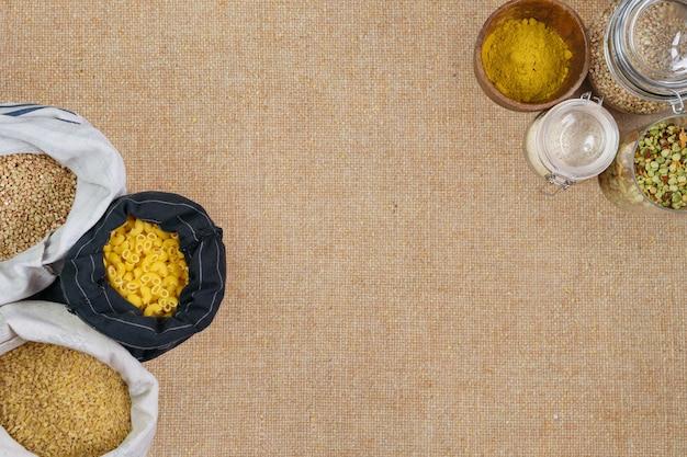 Gezond biologisch voedsel in gerecyclede zakken en plastic vrije banken op linnen achtergrond. afvalvrij winkelen en opslaan. kopieer ruimte