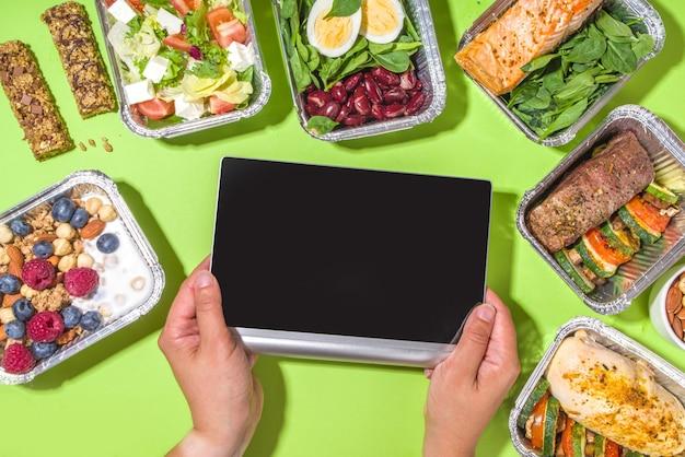 Gezond cateringmenu, lunchboxen voor koeriersmaaltijden. biefstuk vlees, kipfilet, vis en groenten in verpakkingen. dagelijkse levering van een maaltijddieet, afhaalcontainers, online bestelconcept
