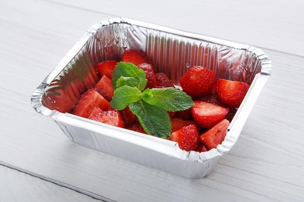 Gezond dessert. de zoete close-up van de aardbeiensalade in de doos van de folielevering.