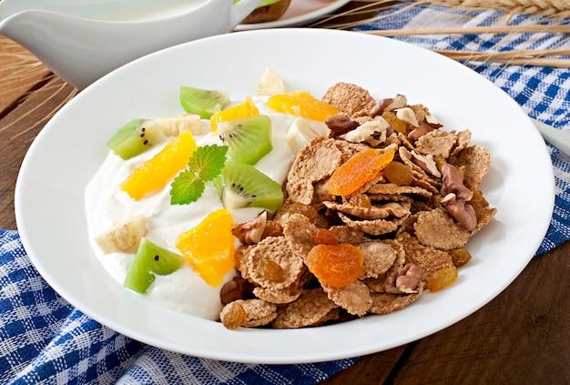 Gezond dessert met muesli en fruit in een witte plaat op de tafel