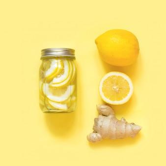 Gezond detoxwater met gember en citrucs in metselaarkruik op punchy geel. wellness.