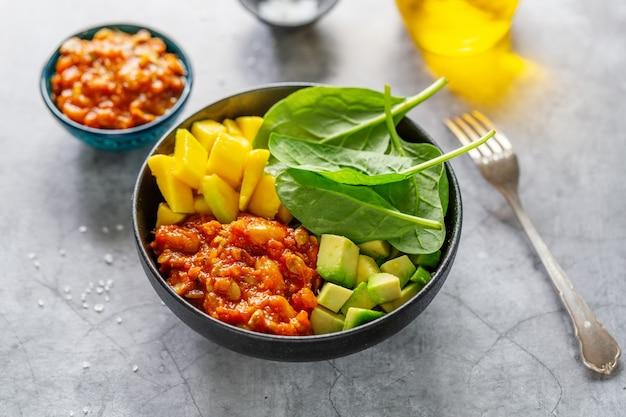 Gezond dieet boeddha kom met groenten en mango geserveerd op plaat op grijze achtergrond. detailopname