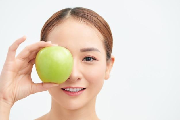 Gezond dieet concept. de aantrekkelijke glimlachende jonge vrouw die verse groene appel houdt behandelde haar ogen in ontbijt op wit