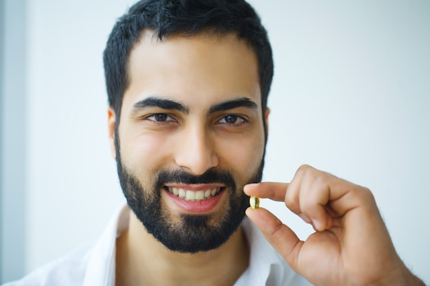 Gezond dieet. voeding. vitaminen. gezond eten, levensstijl. man met visoliecapsules